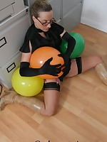 Secretary in the office in stockings playing with balloons